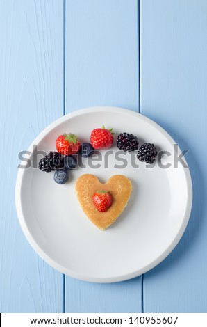 Overhead shot of a heart shaped breakfast pancake underneath an arc of Summer fruits and topped with a cut strawberry.  Food set on a white china plate with a painted wood planked table underneath.