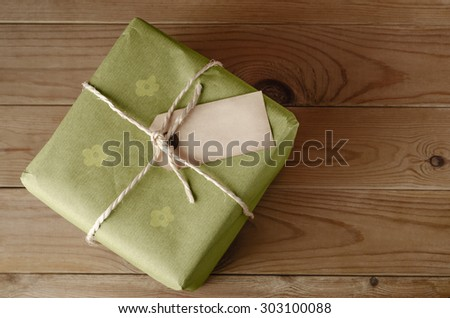 Overhead shot of a parcel, tied with string and wrapped in green floral wrapping paper.  Blank label faces upwards to provide copy space.  Set on an old, worn wooden table. - stock photo