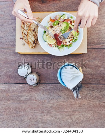 Overhead shot of a person's hands holding cutlery and about to start eating a fresh salad of chicken, avocado, sundried tomatoes and other tasty ingredients on a wooden table - stock photo