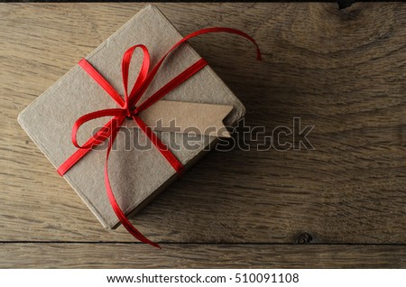 Overhead shot of a plain brown gift box, with Christmas red ribbon and a blank tag for copy space  Set on old Oak wood planking.