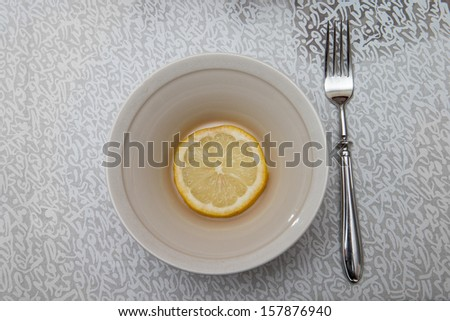 Overhead shot of a plate with a lemon slice and a fork.