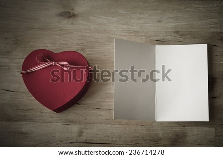 Overhead shot of a red wooden heart-shaped gift box with ribbon bow, and a blank, opened greeting card.Vintage effect with vignette gives appearance of old weathered wooden table beneath. - stock photo