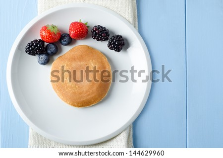 Overhead shot of a round pancake on a white plate, with Summer fruits arranged in an arc above it.  Beneath the plate is a folded hessian cloth on painted light blue wood planked table. - stock photo