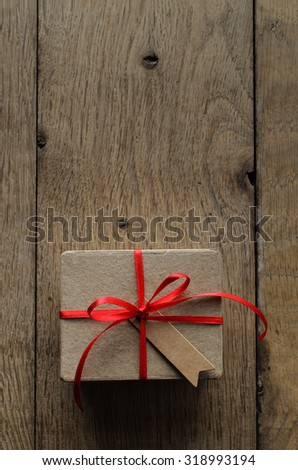 Overhead shot of a simple brown gift box on an old oak wood planked table, tied to a bow with red satin ribbon, with a blank vintage style parcel tag facing upwards. - stock photo