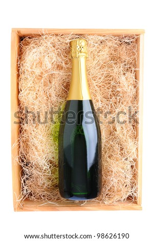 Overhead shot of a single champagne bottle in a wood shipping crate filled with packing straw. Vertical format over a white background - stock photo