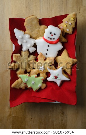 Overhead shot of a variety of plain and iced (frosted) home baked Christmas biscuits (cookies)  in a rectangular white dish with red napkins on wooden table.