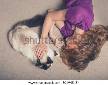 Overhead shot of a young woman lying on a carpet at home and petting a cat - stock photo