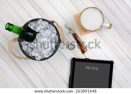 Overhead shot of an ice bucket with an opened beer bottle, a mug of beer and tablet computer for electronic ordering on a rustic white wood table. Horizontal format with copy space. - stock photo