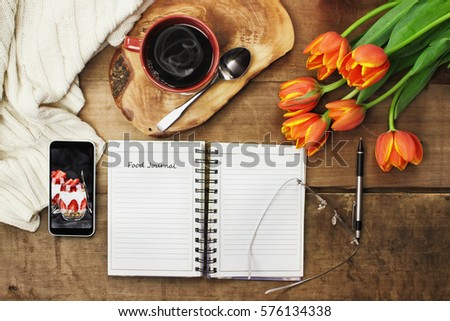 Overhead shot of an open food journal book with cell phone, coffee and flowers over a wood table top ready to plan diet. Flat lay top view style.
