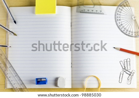 Overhead shot of an opened school exercise book. surrounded by stationery items on a light wood desk. Lined pages provide copy space. - stock photo