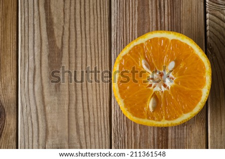 Overhead shot of an orange half with cut side facing upwards, flesh and pips exposed.  Set on right side of frame on a wood planked surface that has been slightly desaturated for a grungy effect. - stock photo