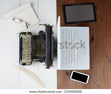 Overhead shot of and old fashioned desk with typewriter and quill pen back-to-back with a modern set up with laptop computer, tablet and cell phone, (Phone and Tablet created in Photoshop - not real) - stock photo