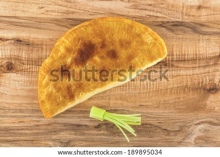 Overhead shot of baked pastry panzerotti and leek on a wooden table. - stock photo