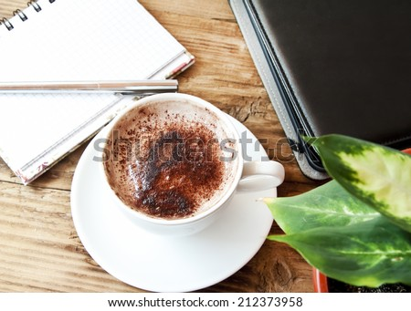 Overhead Shot of Cappuccino Cup . Tablet and Notebook with Pencil and a Green Flower, Office Coffee Break Concept - stock photo