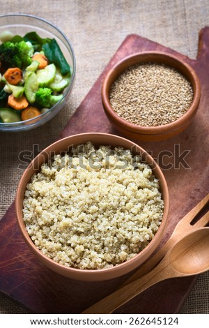 Overhead shot of cooked white quinoa seeds in bowl with sesame and fried vegetables in the back photographed with natural light (Selective Focus, Focus on the quinoa) - stock photo