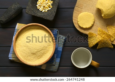 Overhead shot of cornmeal in wooden bowl with corn kernels in mortar, cup of water and cornmeal dough on wooden board, photographed on dark wood with natural light - stock photo