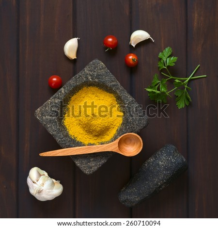 Overhead shot of curry powder spice in mortar with pestle, garlic, cherry tomatoes, parsley leaves on the side, photographed on dark wood with natural light