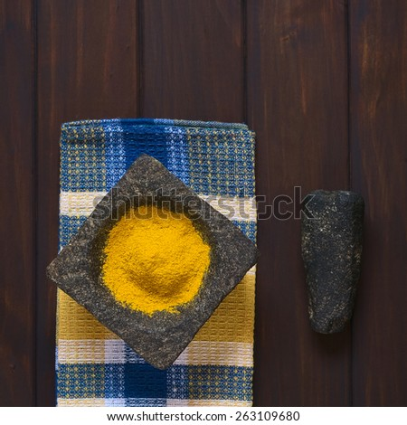 Overhead shot of curry powder spice in mortar with pestle on the side, photographed on dark wood with natural light  - stock photo