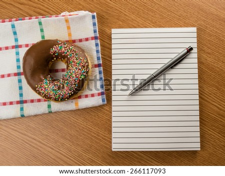 overhead shot of doughnut and notepad with pen on a table