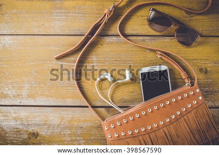 Overhead shot of female bag on an old wooden table - stock photo