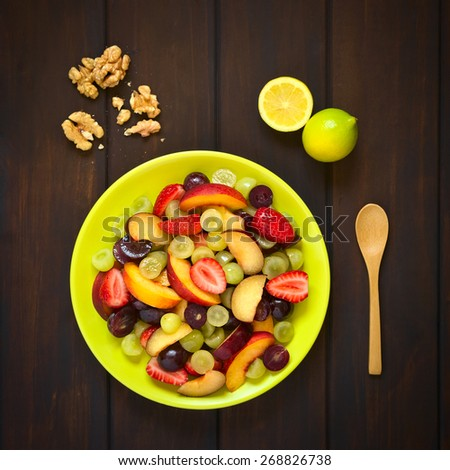 Overhead shot of fresh fruit salad made of grape, strawberry, plum and nectarine served on plate with walnuts, lemon and spoon beside, photographed on dark wood with natural light - stock photo