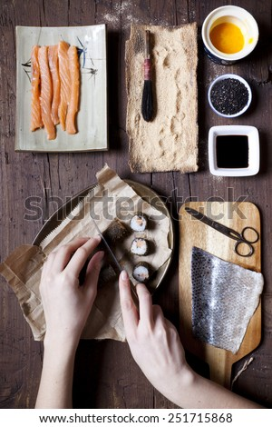 overhead shot of hands slicing a roll of hosomaki sushi and ingredients on table - stock photo
