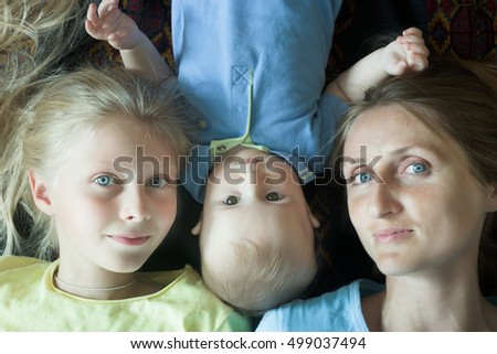 Overhead shot of happy family with mother and two adorable siblings