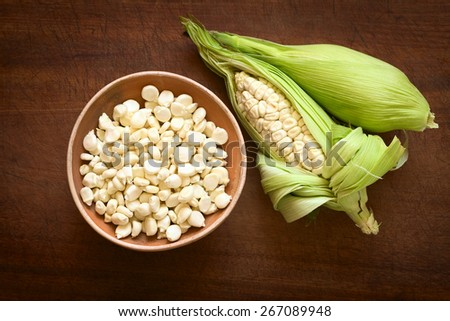 Overhead shot of kernels in bowl and cobs of white corn called Choclo (Spanish), in English Peruvian or Cuzco corn, typically found in Peru and Bolivia, photographed on wooden board with natural light - stock photo