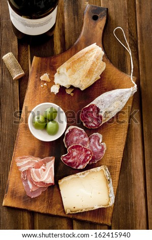 Overhead shot of meat, cheese and a bottle of red wine. - stock photo