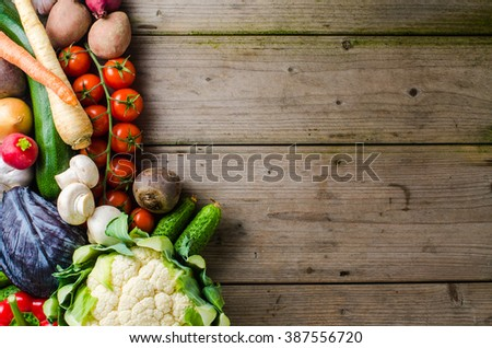Overhead shot of mixed vegetables on wooden table - stock photo