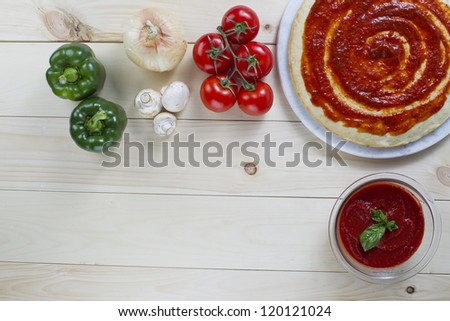 Overhead shot of pizza ingredients on the wooden table - stock photo
