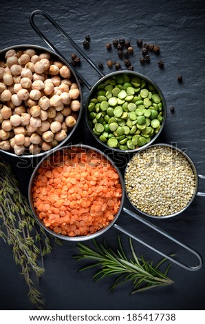 Overhead shot of pulses, chickpeas, lentils, Quinoa and black peppercorns against a stone surface with fresh herbs. Concept image for healthy or vegetarian cooking. - stock photo