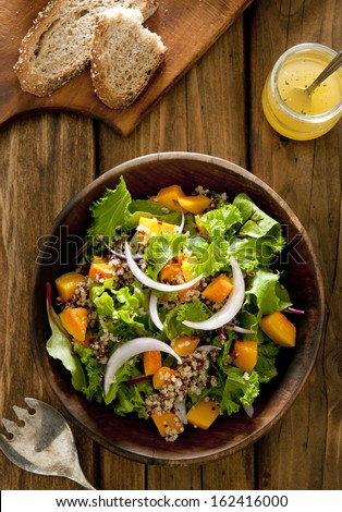 Overhead shot of quinoa salad with butternut squash and oil and vinegar dressing. - stock photo