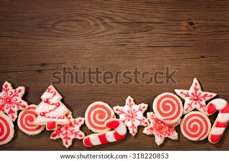 Overhead shot of red and white Christmas cookies border on a wooden background.