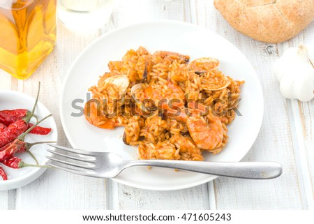 Overhead shot of rice dish with seafood on wooden