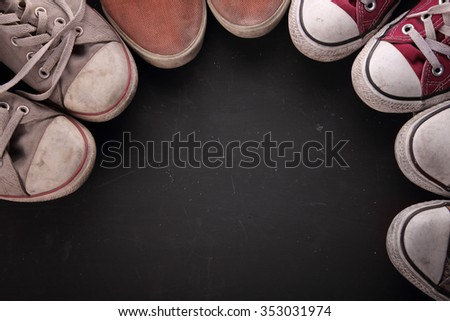 Overhead shot of some dirty sneakers' tips making a circle for copy space on black textured background - stock photo
