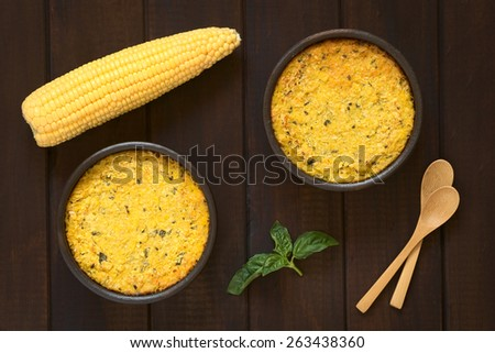 Overhead shot of traditional Chilean corn pie Pastel de Choclo in bowls, photographed on dark wood  with natural light. Below the corn-basil mix is ground meat, olive, boiled egg, raisin, chicken   - stock photo