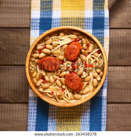 Overhead shot of traditional Chilean dish called Porotos con Riendas (English: beans with reins), made of cooked beans, linguine (flat spaghetti) with fried sausage, photographed with natural light - stock photo