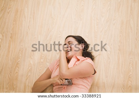 overhead shot of woman lying on back laughing with mobile device in hand