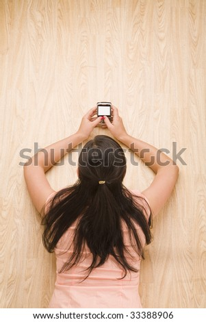 overhead shot of woman using a mobile device - stock photo
