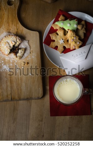 Overhead shot on wooden table of biscuits (cookies), milk and mince pies, left out on Christmas Eve for Santa, with list in envelope.