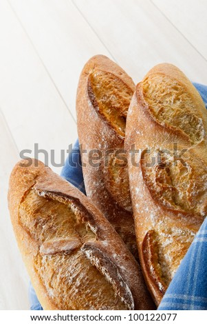 Overhead vertical shot of three fresh baked crusty French Baguettes dusted with flour and wrapped in a blue towel