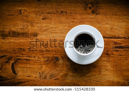 Overhead view black coffee in white cup, wood background.