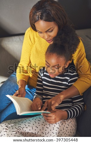 Overhead view mom and daughter reading book sitting in sofa at home