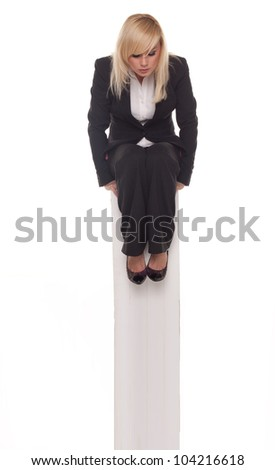 Overhead view of a blonde professional woman sitting relaxing in a black suit with her hands tucked under her knees - stock photo