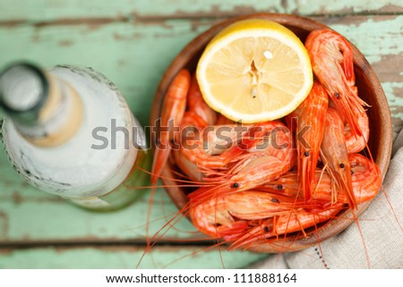 Overhead view of a bowl of cooked shrimp garnished with a half lemon and a bottle of sauce alongside - stock photo
