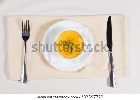 Overhead view of a bowl of delicious spicy pumpkin soup seasoned with cayenne pepper and garnished with herbs served at table - stock photo
