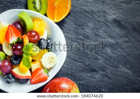 Overhead view of a bowl of fresh fruit salad for a healthy diet made with assorted tropical fruits and an apple, kiwifruit and orange arranged alongside on textured slate with copyspace - stock photo
