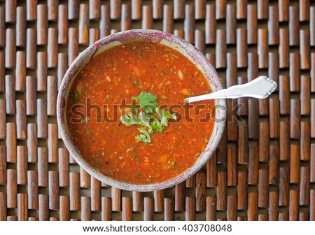 Overhead view of a bowl of freshly made gazpacho soup with cilantro garnish - stock photo