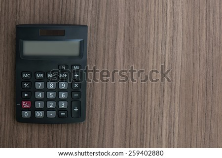 Overhead view of a calculator on a wood desk - stock photo
